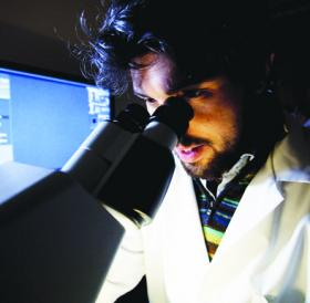 Photograph of student using a microscope